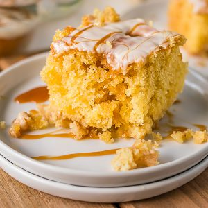 slice of caramel apple poke cake on white plates drizzled with caramel