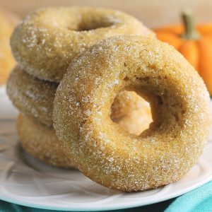 stack of cinnamon sugar pumpkin donuts on white plate
