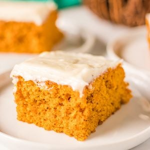 close up shot of a pumpkin bar topped with cream cheese frosting on a white plate