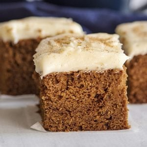 close up of slice of gingerbread cake with thick cream cheese frosting