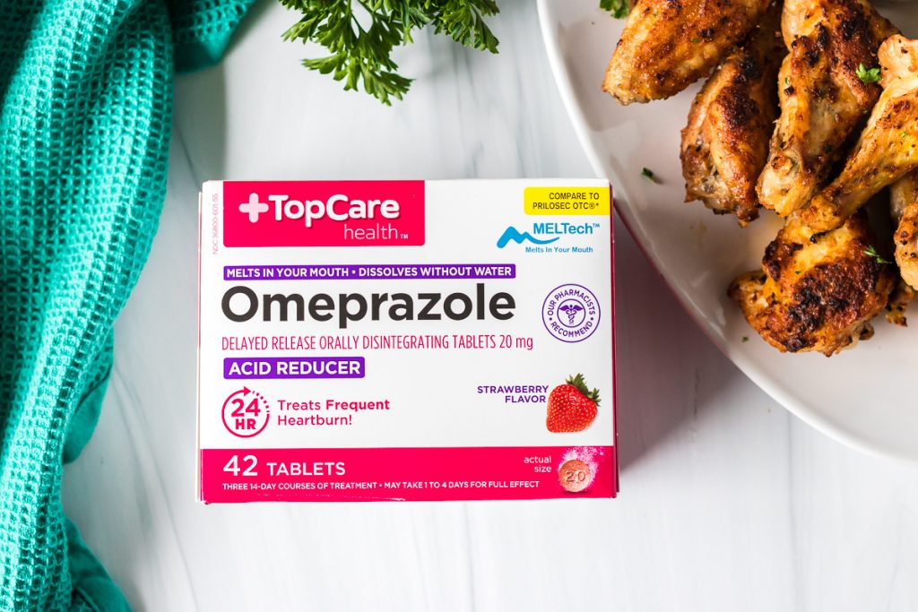 box of topcare omeprazole tablets next to chicken wings
