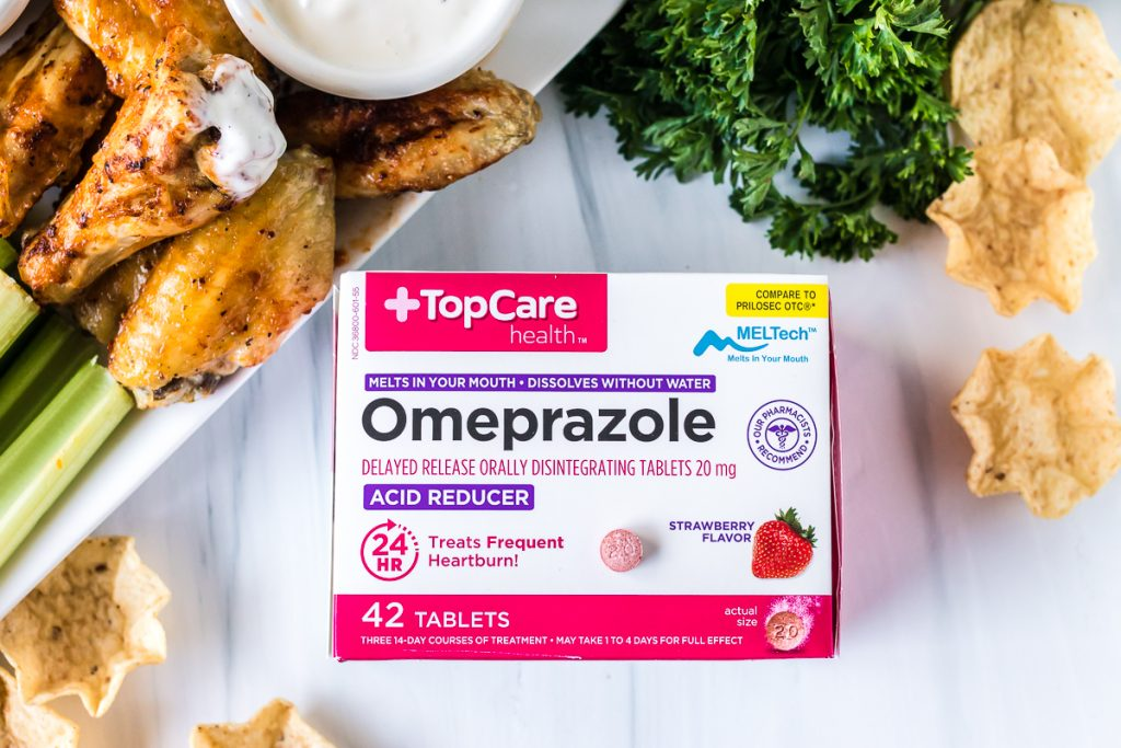 box of omeprazole tablets next to chicken wing platter