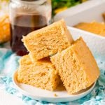white plate of slices of cornbread with honey jar in background