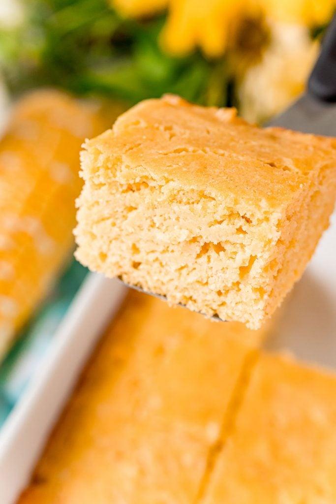 slice of cornbread being raised from baking dish