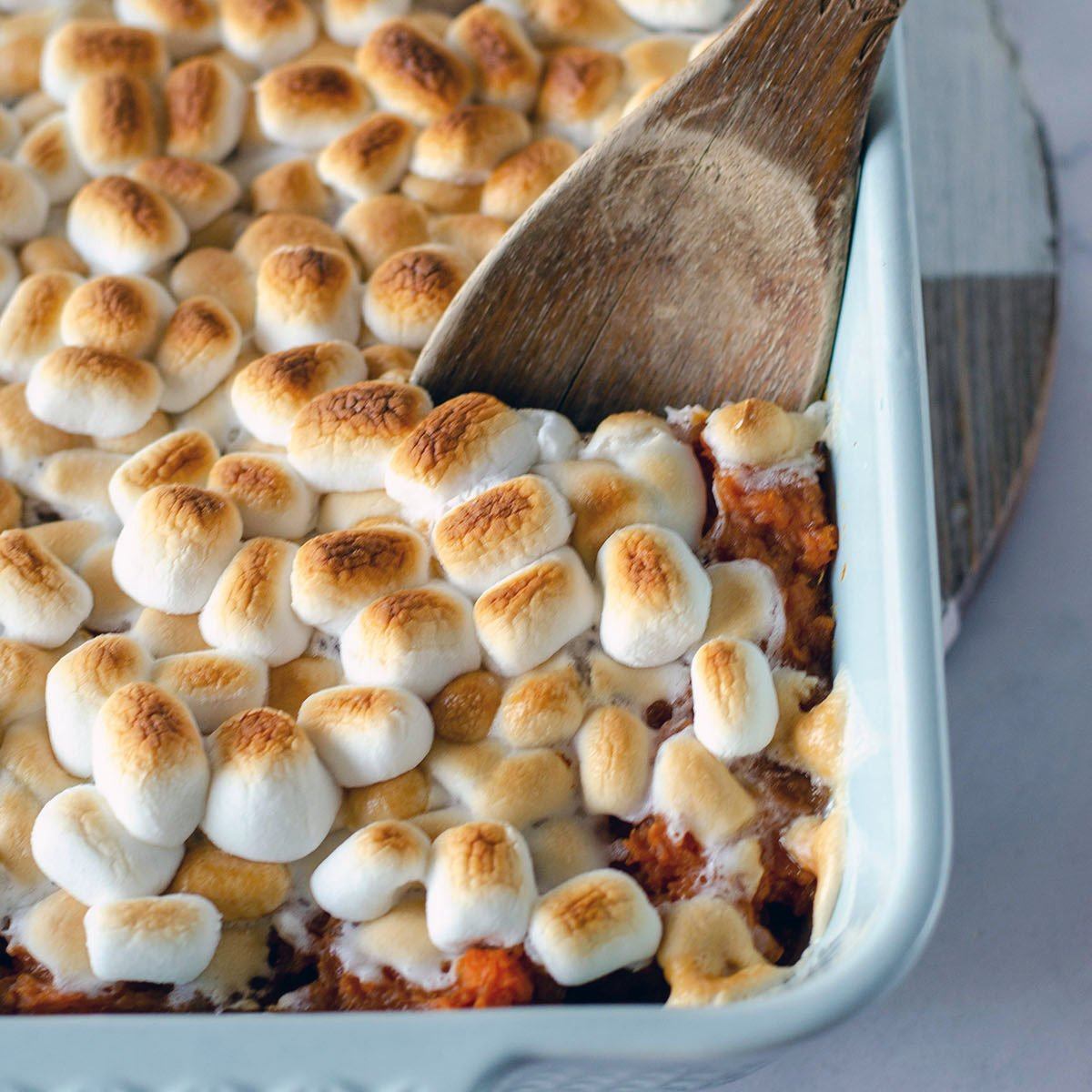 wooden spoon dipping into sweet potato casserole topped with marshmallows