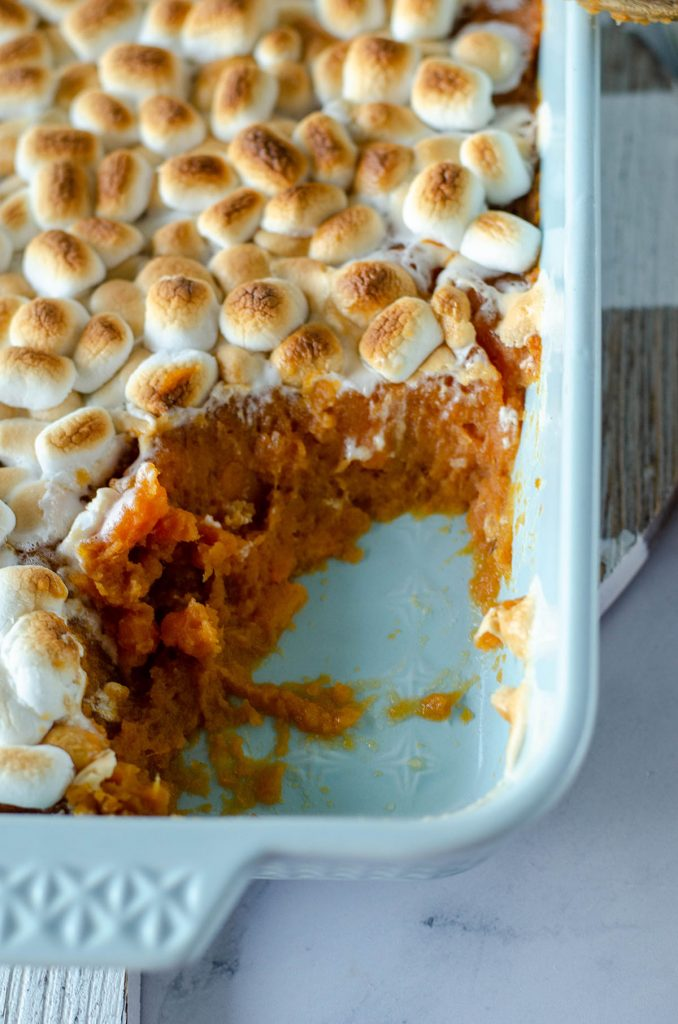 close up of baking dish with scoop of sweet potato casserole missing