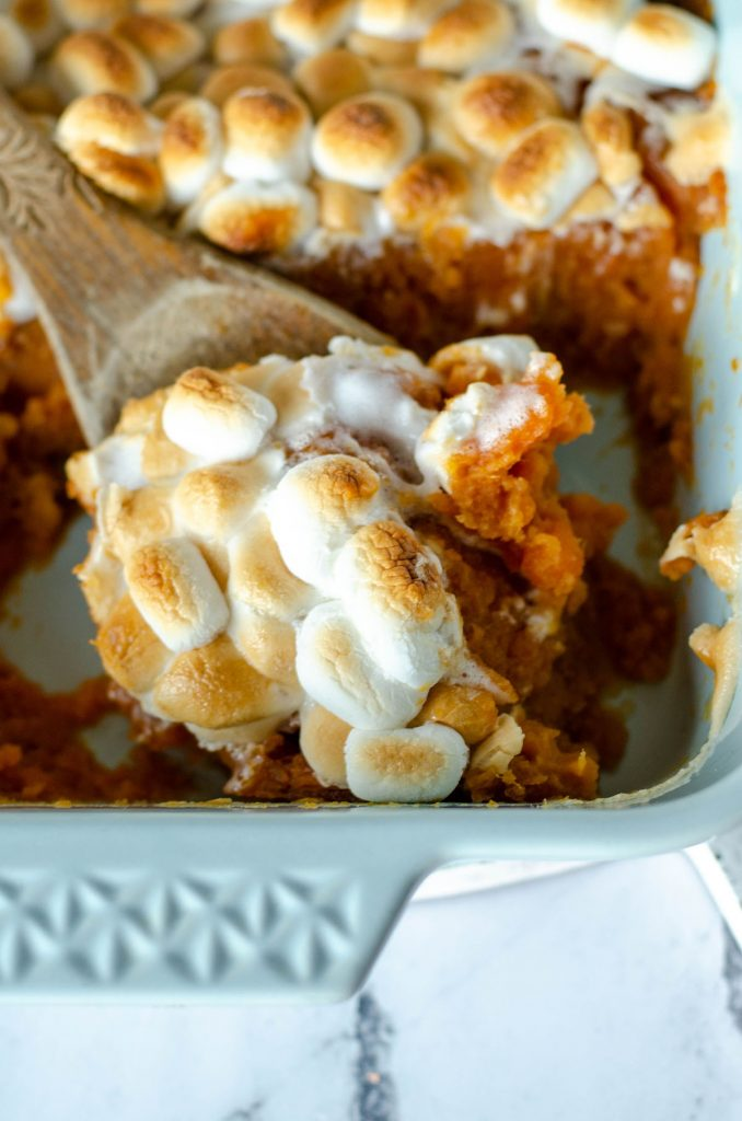 scoop of marshmallow topped sweet potato casserole on wooden spoon