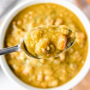 spoon of split pea soup over a bowl