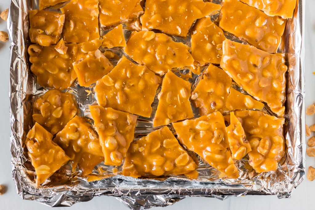 broken peanut brittle on a baking sheet