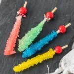 four sticks of rock candy in pink, green, blue, and yellow on a grey slab