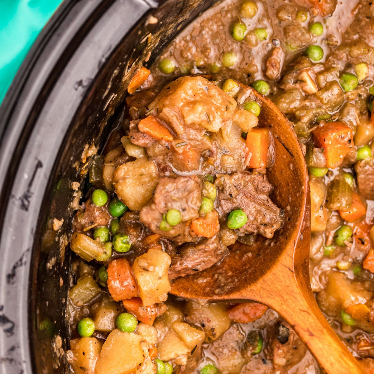 closeup of spoon scooping out slow cooker beef stew from a crockpot