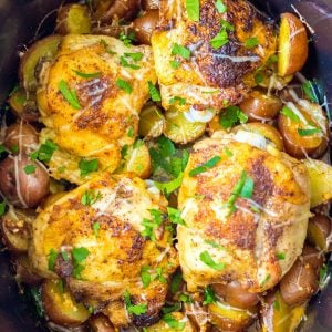 overhead shot of chicken thighs in slow cooker garnished with parsley