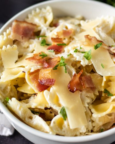 white bowl of bow tie pasta topped with crumbled bacon