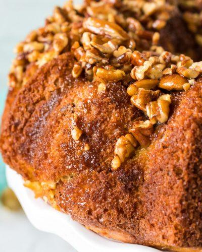 side view of a butter pecan bundt cake on a white cake plate
