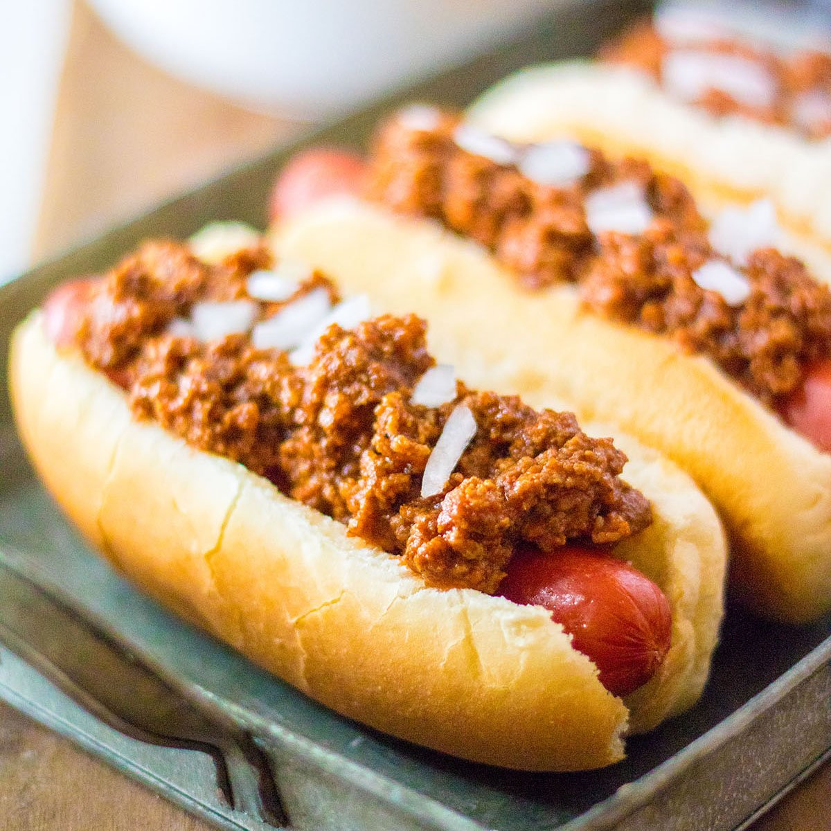 platter of hot dogs topped with chili and onions