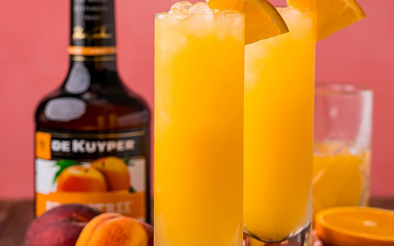 two fuzzy navel cocktails in highball glasses with orange garnish & colorful straws