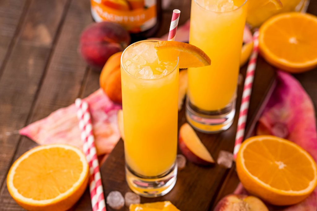 fuzzy navel cocktail surrounded by oranges & peaches