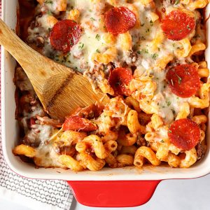wooden spoon scooping pizza pasta bake from a baking dish