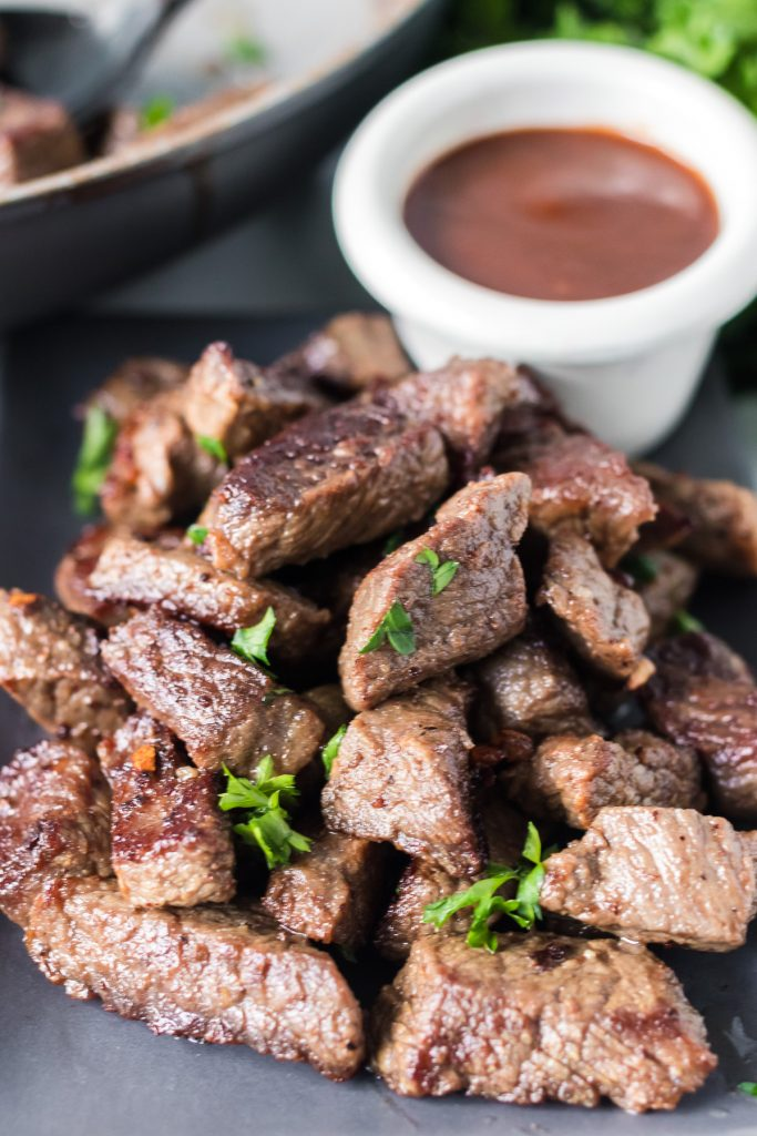 plate of steak bites with a bowl of dip