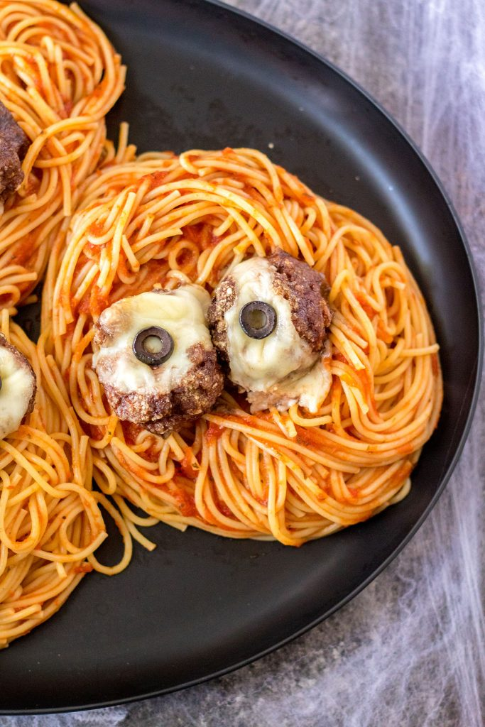 plate of spaghetti topped with spooky eyeball meatballs