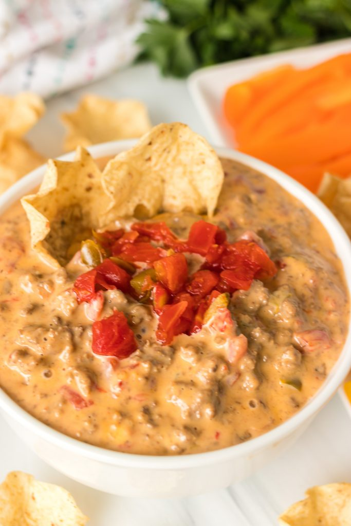 white bowl of beefy rotel dip with chips dipped in