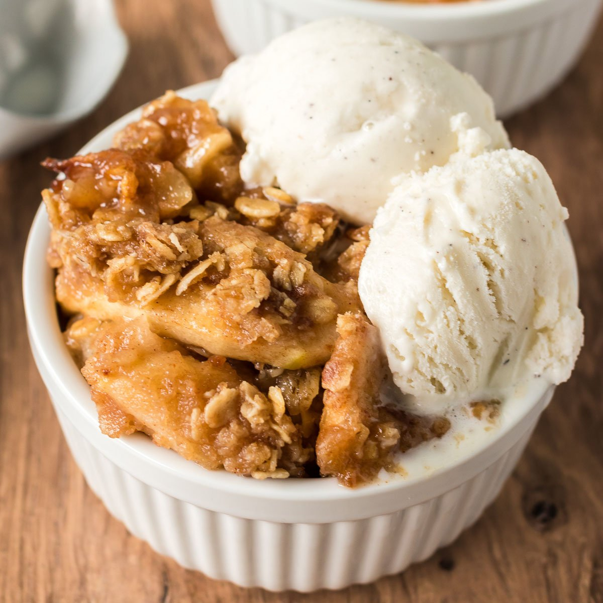 apple crisp topped with vanilla ice cream in a white bowl