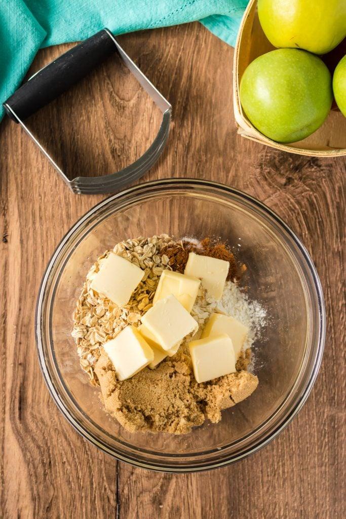 overhead shot of bowl making apple crisp cinnamon oat topping