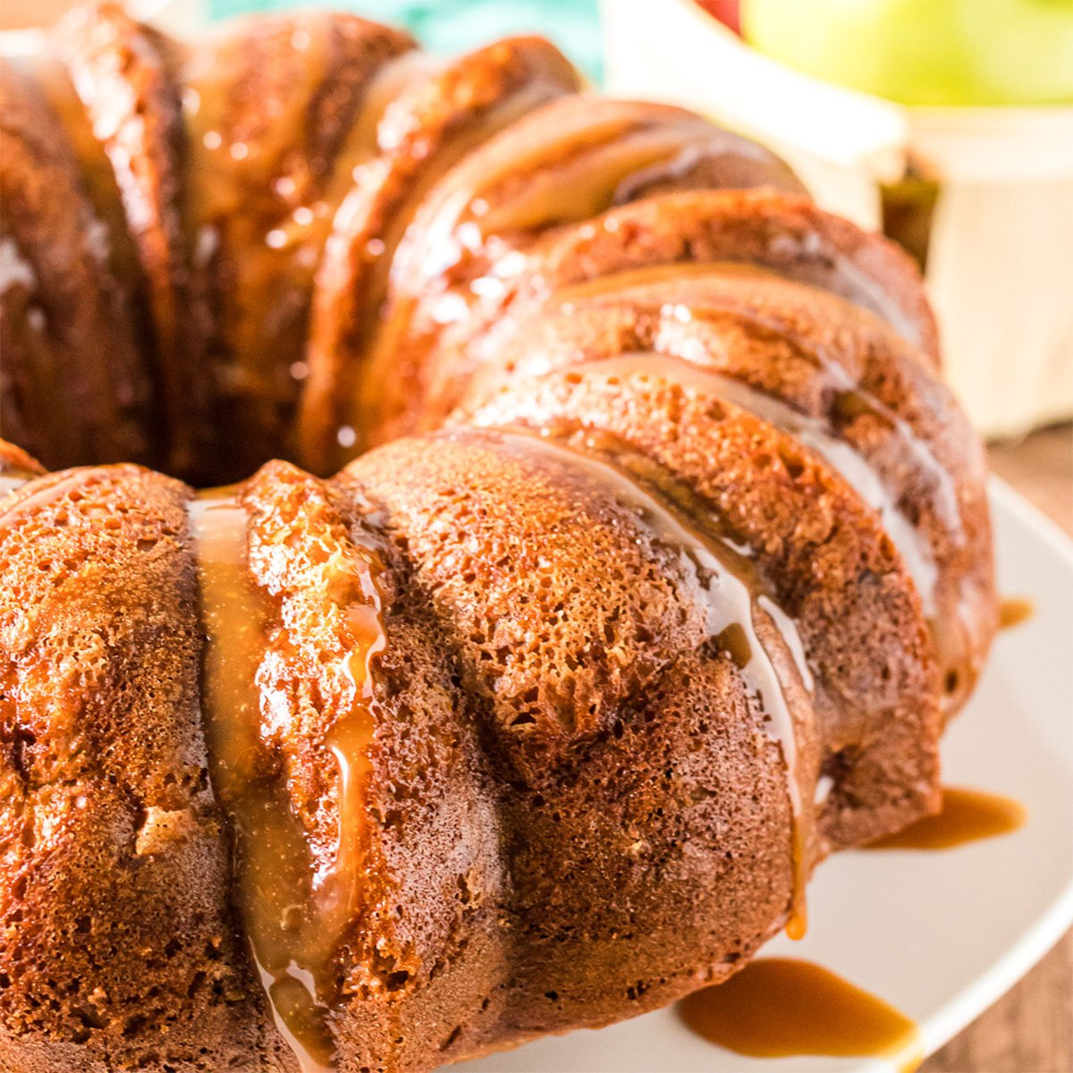 side view of an autumn spice bundt cake dripping with caramel
