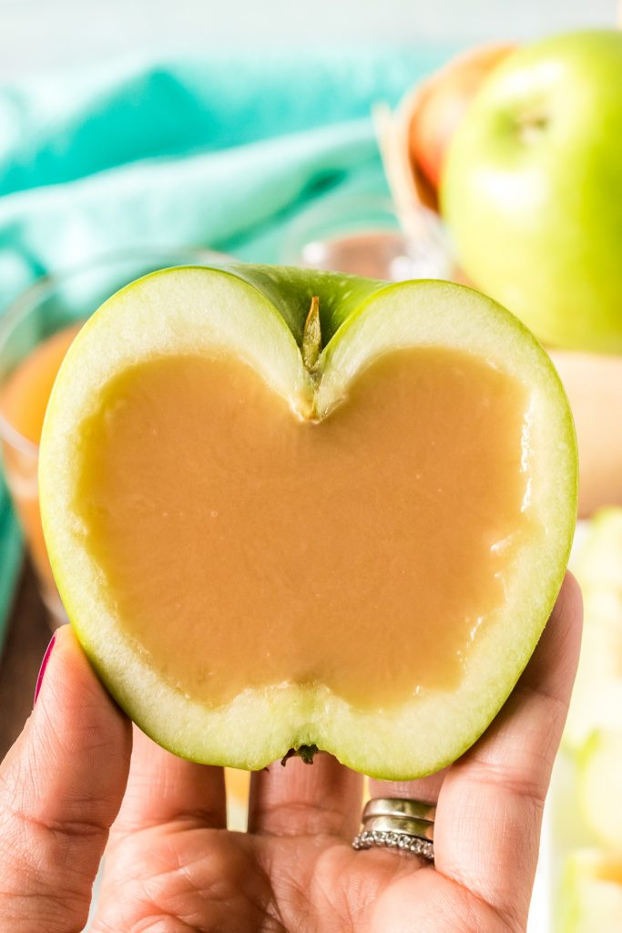 hand holding half an apple filled with caramel
