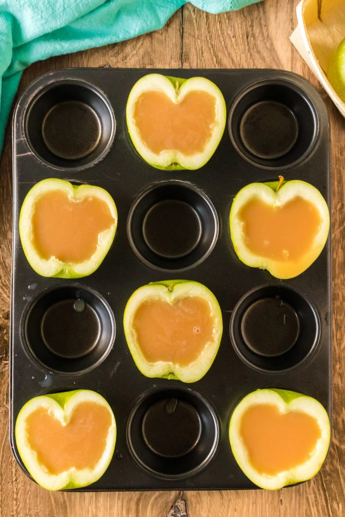 overhead shot of sliced apples in a muffin tin filled with caramel