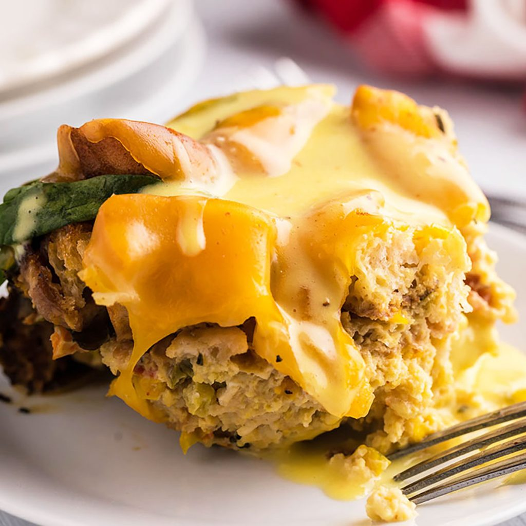 portion of eggs benedict casserole, drizzled with hollandaise, on a white plate with a fork