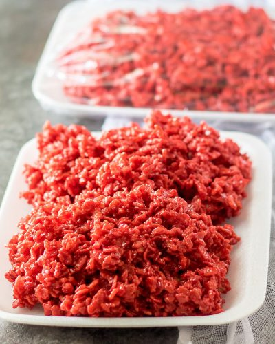 red velvet rice krispies on a white tray that look like raw meat