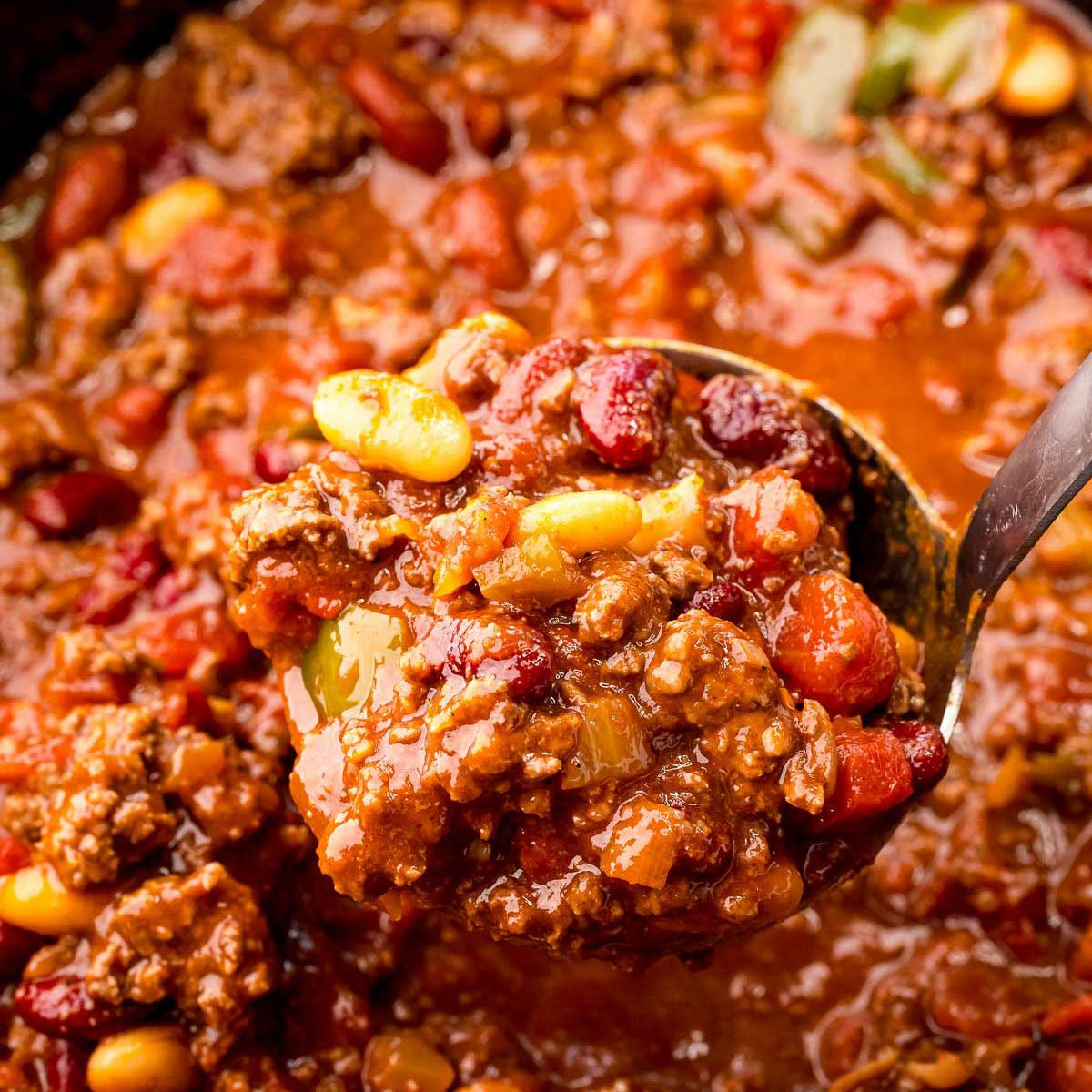 ladle scooping chili from a slow cooker
