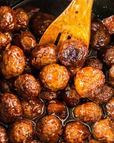 wooden spoon scooping teriyaki meatballs from slow cooker