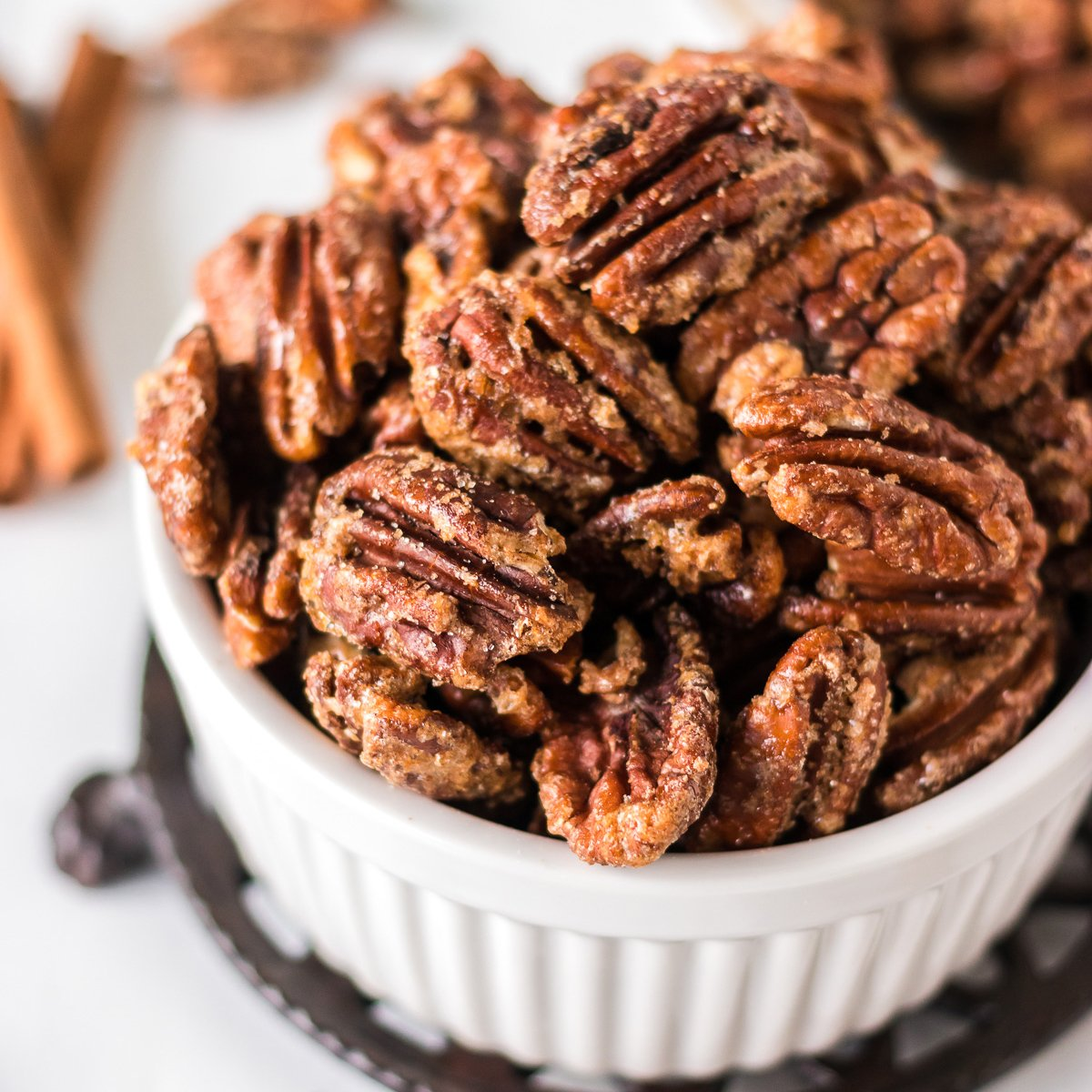 closeup shot of candied pecans in a white bowl
