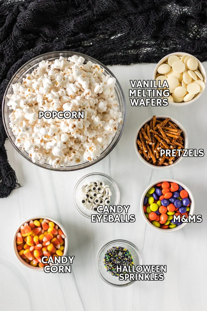 overhead shot of ingredients laid out to make a halloween popcorn mix