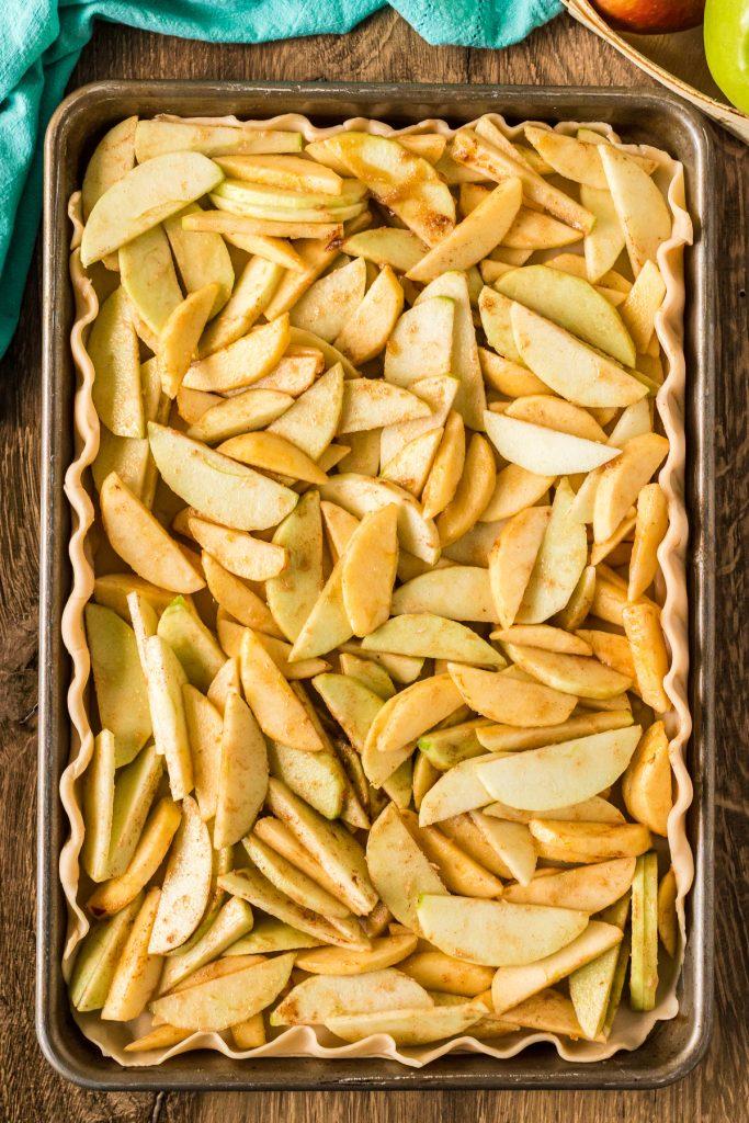 overhead shot of apples in a pie crust in a baking sheet