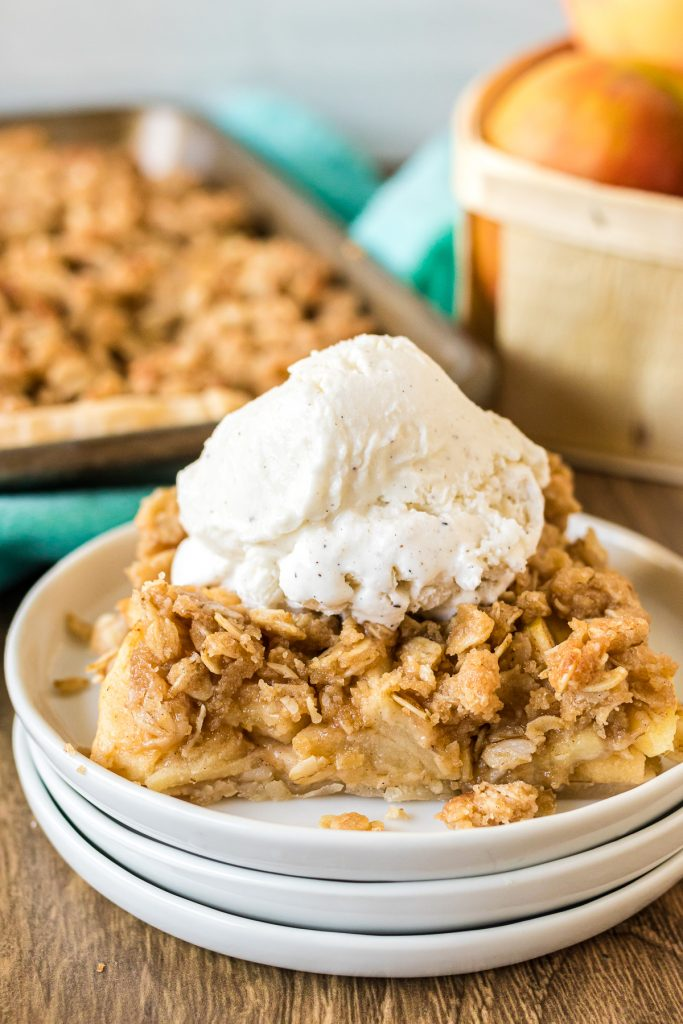 slice of apple slab pie topped with vanilla ice cream on a white plate